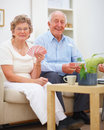 Portrait of a smiling elderly couple playing cards Stock Photography