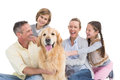 Portrait of smiling family sitting together with their dog Royalty Free Stock Photo