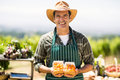 Portrait of a smiling farmer holding box of fruit