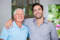 Portrait of smiling father and son with arm around Royalty Free Stock Photo