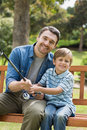 Portrait of a smiling father and son fishing while sitting on park bench Royalty Free Stock Image