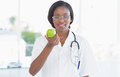 Portrait of a smiling female doctor holding an apple at bright hospital Stock Photography