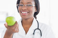 Portrait of a smiling female doctor holding an apple at bright hospital Royalty Free Stock Photos