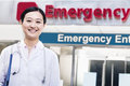 Portrait of smiling female doctor outside of the hospital, emergency room sign in the background Royalty Free Stock Photo
