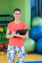 Portrait of smiling female fitness instructor writing in clipboard while standing in gym Royalty Free Stock Photo