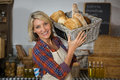 Portrait of smiling female staff carrying wicker basket of various breads at counter Royalty Free Stock Photo