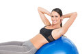 Portrait of a smiling fit woman stretching on fitness ball Royalty Free Stock Photo