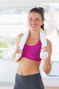 Portrait of a smiling fit woman with towel in gym young standing the Royalty Free Stock Photos