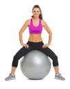 Portrait of smiling fitness young woman on fitness ball isolated white Stock Photography