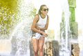 Portrait of Smiling Funny African American Teenager Girl with Dreadlocks Enjoying in Fountain Outdoors