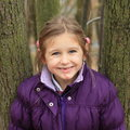 Portrait of smiling girl cute little kid clothed in lila winter jacket in forest Stock Photos