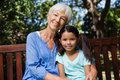 Portrait of smiling girl and grandmother sitting on wooden bench
