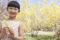 Portrait of smiling girl holding a yellow flower in the park in springtime Royalty Free Stock Image