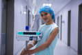 Portrait of smiling girl with iv drip standing in corridor Royalty Free Stock Photo