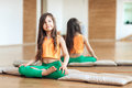 Portrait of smiling girl practicing yoga, sitting in Padmasana exercise, working out wearing sportswear