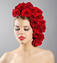 Portrait of smiling girl with red roses hairstyle light background Royalty Free Stock Images
