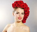 Portrait of smiling girl with red roses hairstyle light background Royalty Free Stock Photos