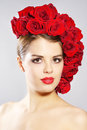 Portrait of smiling girl with red roses hairstyle light background Royalty Free Stock Image