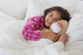 Portrait of a smiling girl with stuffed toy resting in bed Royalty Free Stock Photo