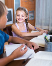 Portrait of smiling girl writing homework with brother Stock Photos
