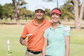 Portrait of smiling golfer couple with arm around Royalty Free Stock Photo