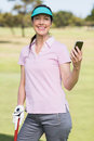 Portrait of smiling golfer woman using phone Royalty Free Stock Photo