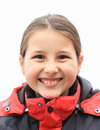 Portrait of smiling and grinning girl cute little kid clothed in red winter jacket Royalty Free Stock Photo