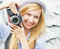 Portrait of smiling hipster girl making photo with retro camera in hat Royalty Free Stock Photography