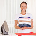 Portrait of smiling housewife ironing clothes. Royalty Free Stock Photo