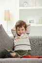 Portrait of smiling kid sitting on sofa at home caucasian indoor looking camera Stock Image