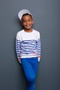 Portrait of a smiling little boy standing against gray background Stock Image