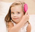 Portrait of smiling little girl brushing her hair closeup Royalty Free Stock Image