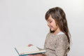 Portrait of smiling little girl reading a book Royalty Free Stock Photo