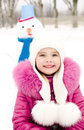 Portrait of smiling little girl with snowman