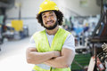 Portrait of smiling male manual worker standing arms crossed in industry Royalty Free Stock Photo