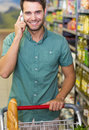 Portrait of smiling man buy food and phoning at supermarket Stock Image