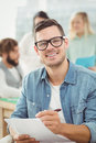 Portrait of smiling man holding paper and pen Royalty Free Stock Photo