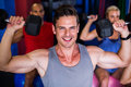 Portrait of smiling man lifting dumbbell in gym Royalty Free Stock Photo