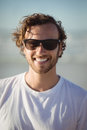 Portrait of smiling man wearing sunglasses at beach Royalty Free Stock Photo