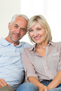 Portrait of a smiling mature couple at home sitting on sofa Royalty Free Stock Photos