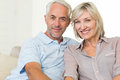 Portrait of a smiling mature couple at home sitting on sofa Stock Image