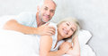 Portrait of a smiling mature couple lying in bed women and men at the home Royalty Free Stock Images
