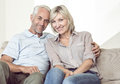Portrait of smiling mature couple sitting on sofa a with arm around at home Royalty Free Stock Images