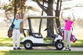 Portrait of smiling mature golfer couple with arms raised Royalty Free Stock Photo