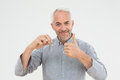 Portrait of a smiling mature man with keys gesturing thumbs up over white background Royalty Free Stock Images