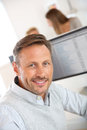 Portrait of smiling mature man in office cheerful sitting and working on desktop Royalty Free Stock Photography
