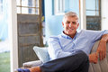 Portrait Of Smiling Mature Man Sitting On Sofa At Home Royalty Free Stock Photo