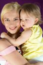Portrait of smiling mother with baby daughter hugging her Stock Photography