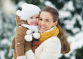 Portrait of smiling mother and baby in winter park high resolution photo Stock Photo
