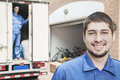 Portrait of smiling mover with moving truck in the background Stock Photography